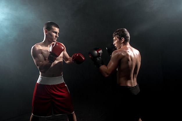 Dwóch profesjonalnych bokserów na czarnym dymie