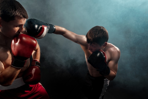 Dwóch profesjonalnych bokserów na czarnym dymnym,