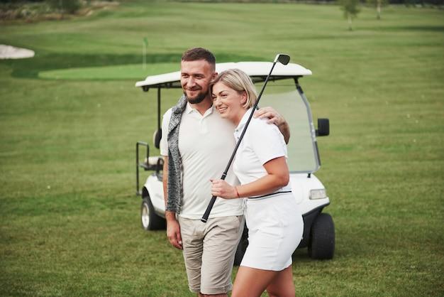 Dwóch profesjonalnych golfistów, kobieta i mężczyzna idą razem do następnej dziury. miłośnicy przytulają się i uśmiechają, mają randkę