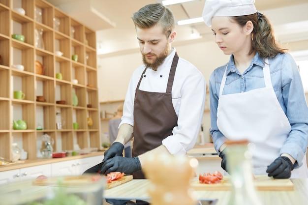 Dwóch profesjonalnych kucharzy gotujących w restauracji