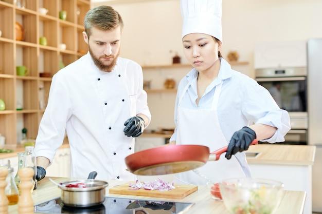 Dwóch profesjonalnych kucharzy w pracy w kuchni