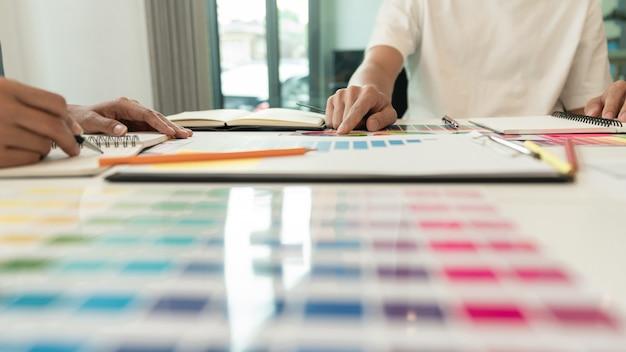 Dwóch projektantów dyskutuje o kolorystyce dla doskonałej pracy wizualnej.