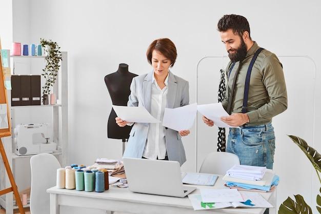 Dwóch projektantów mody pracuje nad nową linią odzieży w atelier