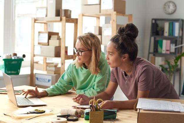 Dwóch projektantów mody używa laptopa do zaprojektowania nowego projektu online w warsztacie