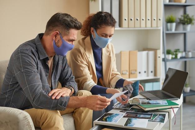 Dwóch projektantów w maskach ochronnych pracuje w zespole nad profesjonalnymi zdjęciami podczas spotkania w biurze