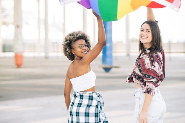 Dwóch protestujących przyjaciół idzie radośnie, trzymając flagę lgbt
