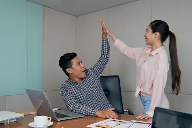 Dwóch przedsiębiorców rozpoczynających działalność daje piątkę z okazji udanej transakcji