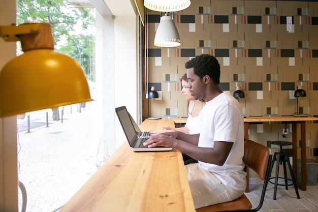 Dwóch przemyślanych projektantów pracujących na laptopach i siedzących przy stole w pobliżu okna