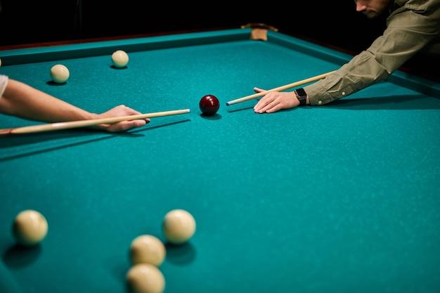 Dwóch przyciętych mężczyzn grających w snookera lub przygotowujących się do strzelania do bil bilardowych na stole bilardowym