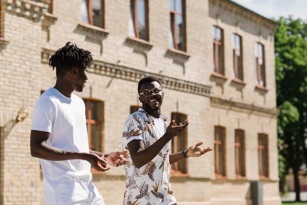 Dwóch przyjaciół afroamerykanów spaceruje po mieście, śmiejąc się i rozmawiając na różne tematy. szczęśliwi ludzie.