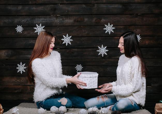 Dwóch przyjaciół całkiem młodych śmieszne kobiety uśmiechnięte i dobrze się bawić, trzymając jasne prezenty świąteczne, gotowe do świętowania.