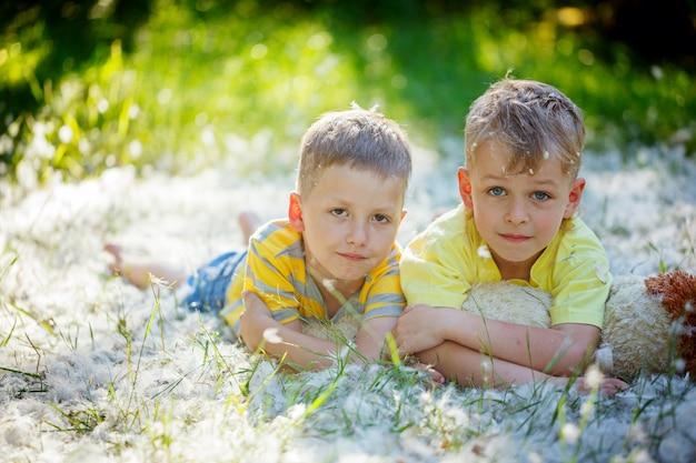 Dwóch przyjaciół chłopców w przytulanie i leżąc na trawie w lecie