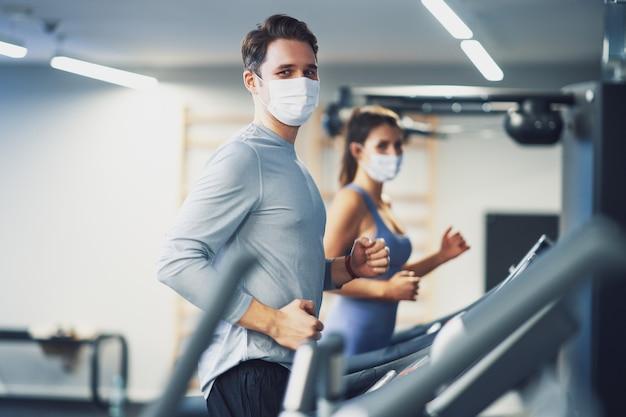Dwóch przyjaciół ćwiczących na bieżni w maskach z powodu covid-19