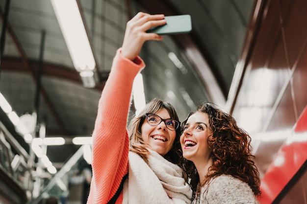 Dwóch przyjaciół czeka schodząc po schodach na stację przed złapaniem pociągu. robienie selfie telefonem komórkowym. fotografia podróżnicza