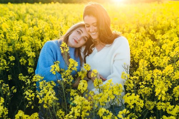 Dwóch przyjaciół czule przytulających się na polu rzepaku o zachodzie słońca.