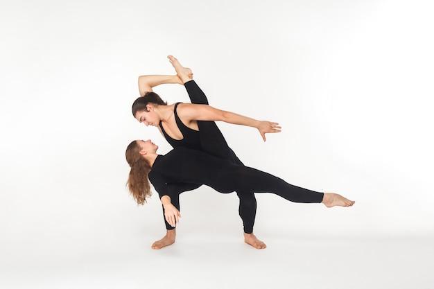 Dwóch przyjaciół elastyczności tańczy, robi występ. strzał studio, na białym tle
