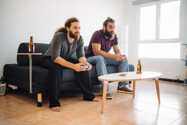 Dwóch przyjaciół gra w gry wideo w salonie, siedząc na sofie