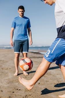 Dwóch przyjaciół gry w piłkę nożną na plaży