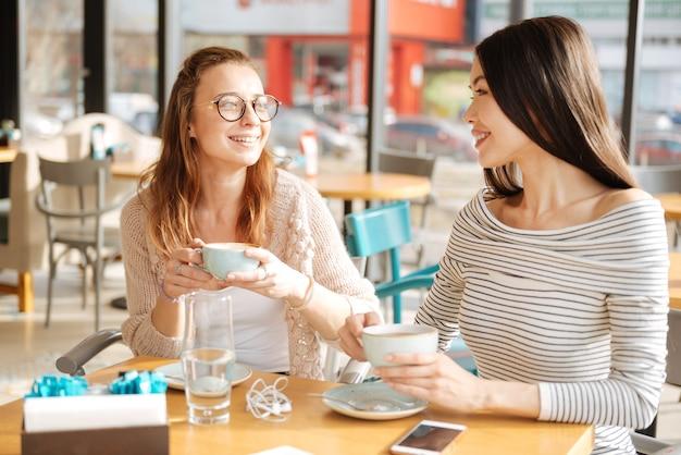 Dwóch przyjaciół. kilka dziewczyn patrzy na siebie siedząc w kawiarni i trzymając filiżanki z kawą.