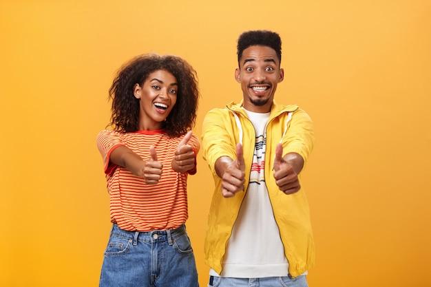 Dwóch przyjaciół lubi idealny i niesamowity plan portret radosnej, przyjaznej, optymistycznej afroamerykanki i mężczyzny, pokazując kciuki w górę w geście aprobaty i zgody, uśmiechając się szeroko