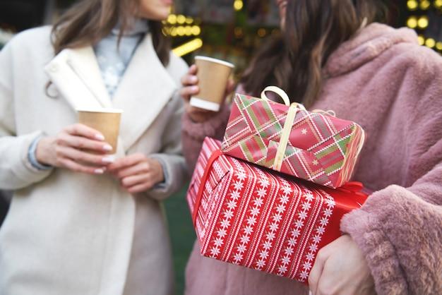 Dwóch przyjaciół na jarmarku bożonarodzeniowym niosących prezenty świąteczne
