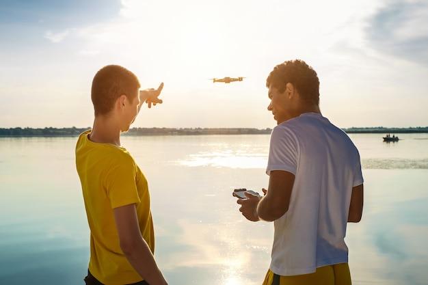 Dwóch przyjaciół obsługujących drona z kontrolerem stojącym w pobliżu rzeki