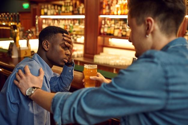 Dwóch przyjaciół płci męskiej pije piwo przy ladzie w barze. ludzie relaksują się w pubie, nocnym stylu życia, przyjaźni, uroczystościach