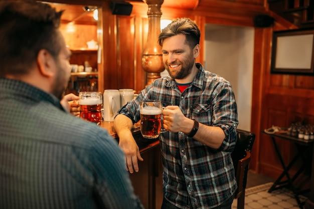 Dwóch przyjaciół płci męskiej pije piwo przy ladzie w pubie