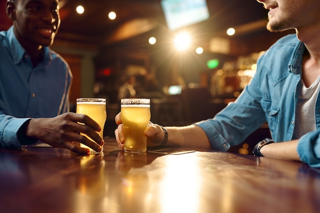 Dwóch przyjaciół płci męskiej pije świeże piwo w barze. ludzie relaksują się w pubie, nocnym stylem życia, przyjaźni, uroczystościach, męskich wakacjach w restauracji