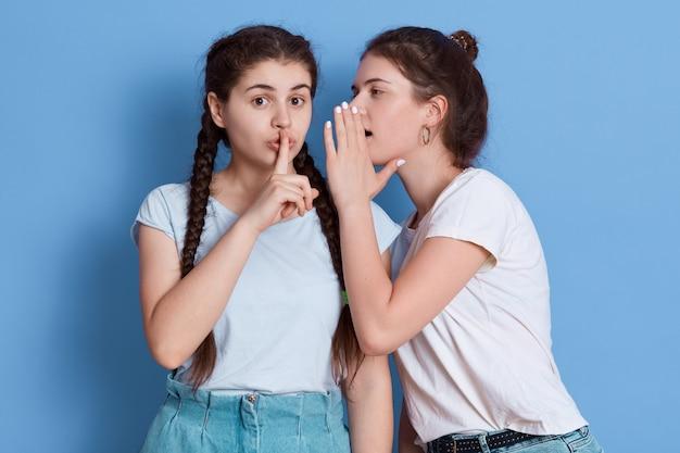 Dwóch przyjaciół plotkuje na białym tle nad niebieską przestrzenią