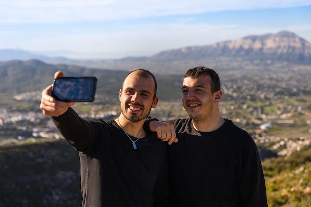Dwóch przyjaciół robiących sobie autoportret telefonem komórkowym, w słoneczny dzień z kilkoma chmurami, na górze między wioskami, dwóch ciemnowłosych chłopców rasy kaukaskiej w ciemnych ubraniach.