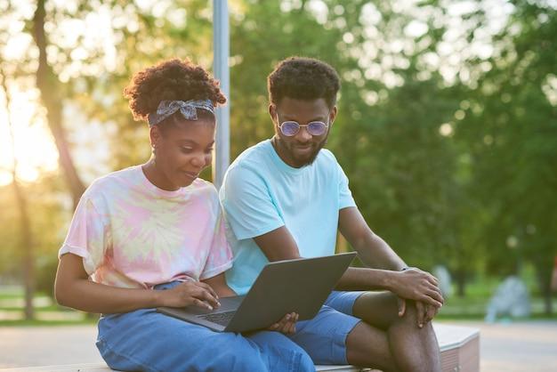 Dwóch przyjaciół siedzących na ławce i razem korzystających z laptopa w parku