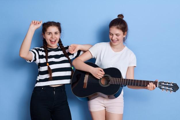 Dwóch przyjaciół śpiewających i tańczących na białym tle, pani z grą na gitarze, urocza dziewczyna w t-shirt w paski i warkocze podnoszące ręce.