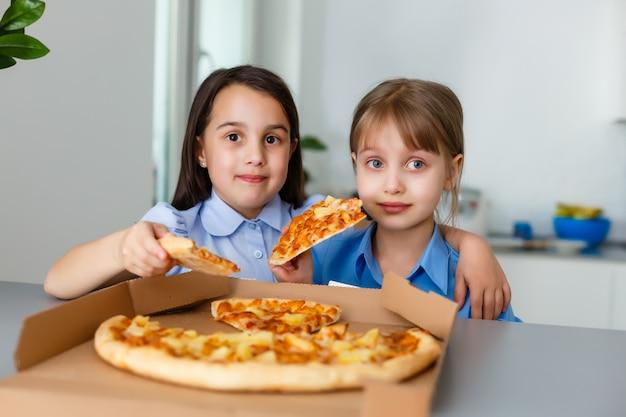 Dwóch przyjaciół szczęśliwy małe dziecko dziewczynka jedzenie pizzy plastry
