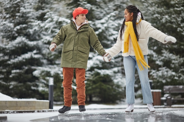 Dwóch przyjaciół w ciepłych ubraniach spędzających wolny czas na łyżwach na lodowisku