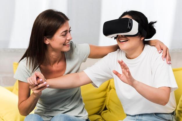 Dwóch przyjaciół w domu korzystających z zestawu słuchawkowego wirtualnej rzeczywistości