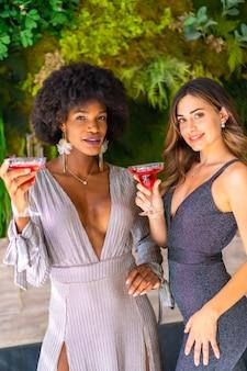 Dwóch przyjaciół w galowych sukienkach przy koktajlu na przyjęciu w hotelu, styl życia. styl życia w stylu glamour, ekskluzywna impreza
