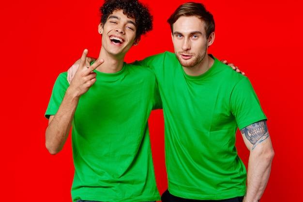 Dwóch przyjaciół w zielonych koszulkach przytula zabawną czerwień