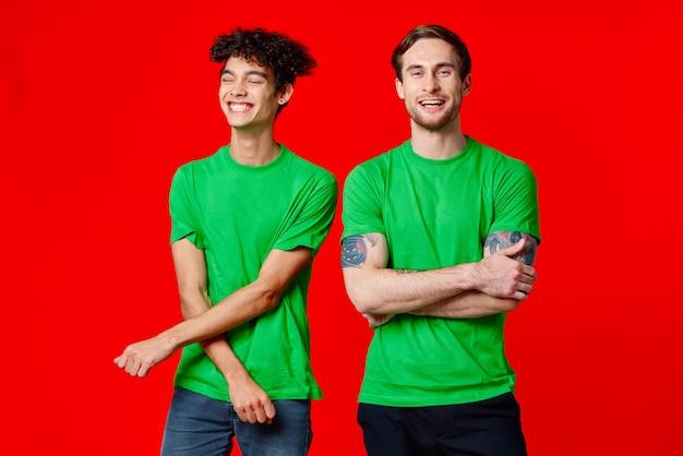 Dwóch przyjaciół zielone koszulki komunikacja styl życia czerwone tło