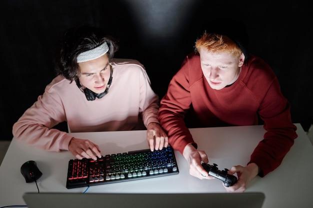 Dwóch przyjaznych facetów w codziennym ubraniu, grających w gry komputerowe, siedzących w ciemności przy biurku przed monitorem