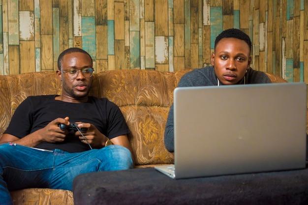 Dwóch przystojnych afrykańczyków siedzi na kanapie, grając w gry wideo za pomocą joysticka, gamepada, padu