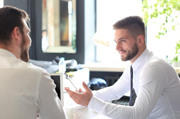 Dwóch przystojnych biznesmenów pracujących razem nad projektem, siedząc przy stole w biurze.