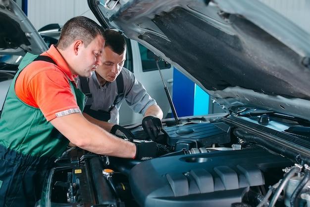 Dwóch przystojnych mechaników w mundurach pracuje w serwisie samochodowym. naprawa i konserwacja samochodów.