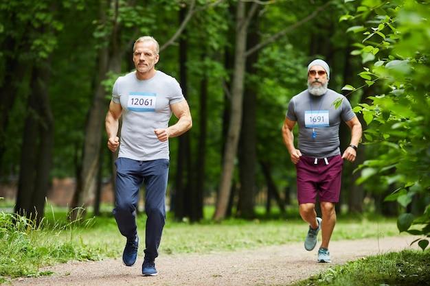 Dwóch przystojnych mężczyzn w wieku sportowym biorących udział w wyścigu maratońskim w parku miejskim w letni dzień, szerokie ujęcie