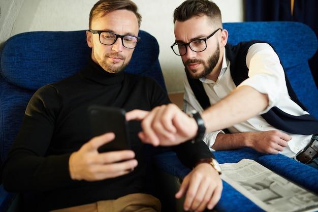 Dwóch przystojnych mężczyzn za pomocą smartfona