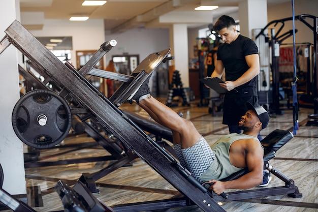 Dwóch przystojnych mężczyzn zajmuje się siłownią