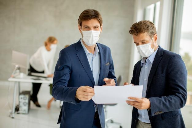 Dwóch przystojnych młodych biznesmenów z maskami ochronnymi na twarz, omawiając papierowy plan w biurze