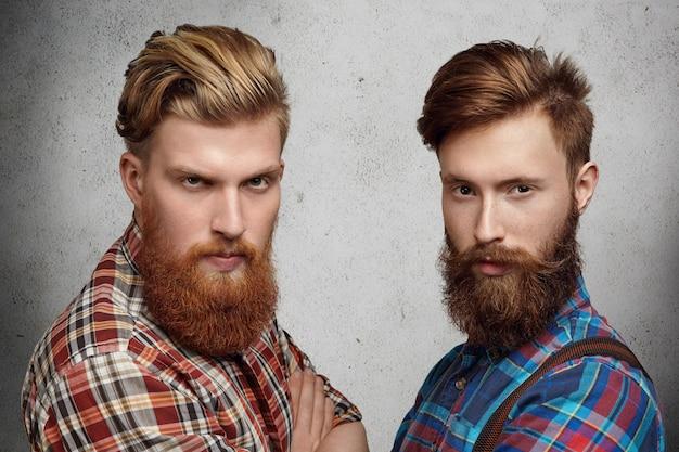 Dwóch przystojnych młodych, nieogolonych mężczyzn z brodami hipsterów, ubrani w stylowe koszule w kratę, stojących z założonymi rękami na szarej betonowej ścianie, patrzących z poważnym wyrazem twarzy, mrużących oczy