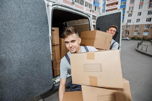 Dwóch przystojnych pracowników w mundurach rozładowuje furgonetkę pełną pudeł