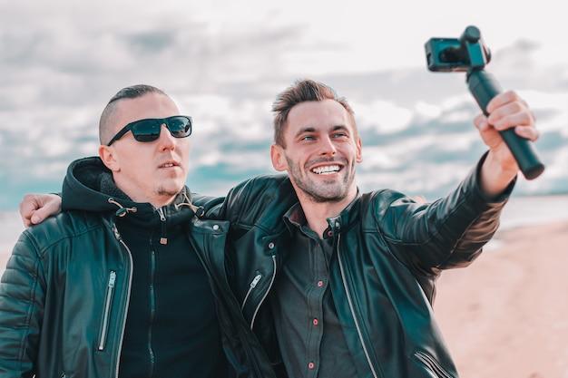 Dwóch przystojnych uśmiechniętych przyjaciół robi selfie przy użyciu kamery sportowej ze stabilizatorem gimbala na plaży.